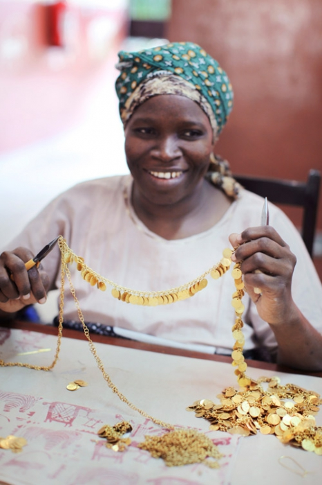 An artsian hand crafts jewellery for People Tree at Bombolulu, a Fair Trade organization in Kenya