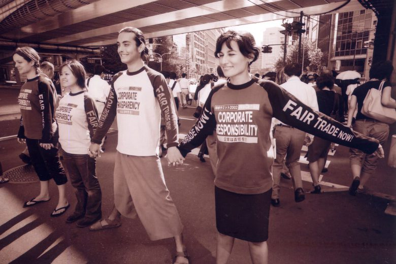 Safia Minney and colleagues holding hands and forming a line in protest in Tokyo. They wear t-shirts calling for corporate transparency and corporate responsibility and fair trade